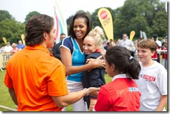 "First Lady Michelle Obama hugs former Olympic gymnast Nastia Liukin during a ""Let's Move! London"" event at Winfield House in London, England, July 27, 2012. Olympic short track speedskater Apolo Anton Ohno, orange looks on. (Official White House Photo by Sonya N. Hebert)"
