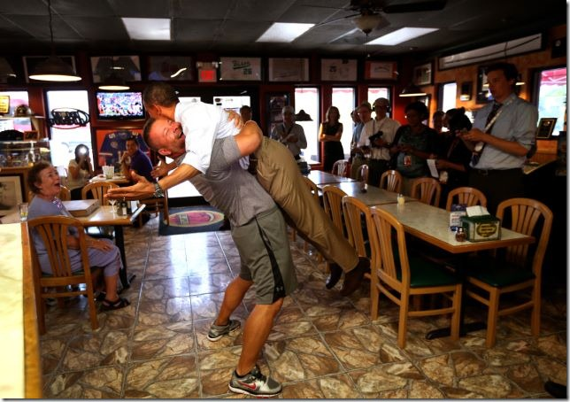 President Obama is lifted in the air by Scott Van Duzer, owner of the Big Apple Pizza owner. Photo by Doug Mills of the New York Times.